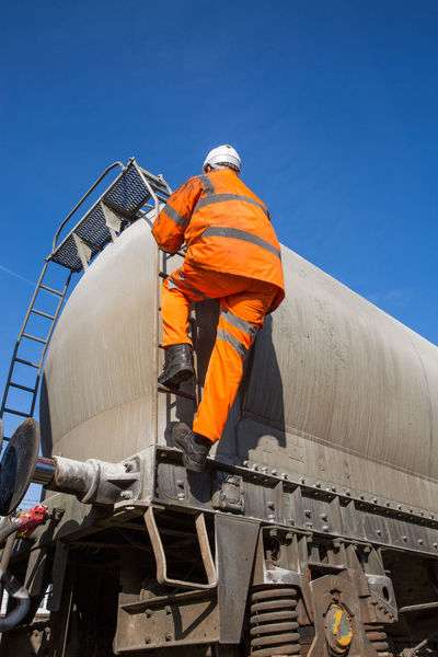 A railway worker wearing hi viz clothing and climbing up onto a large rail freight tanker in a health and safety at work image. Climb High Ladder Railroad Track Tanker Work Worker Working At Heights Climbing Danger Dangerous Freight Train Freight Transportation Health And Safety Hi Viz High Visibility Occupation Protective Workwear Railroad Railway Railway Track Safety Track Train Workers At Work
