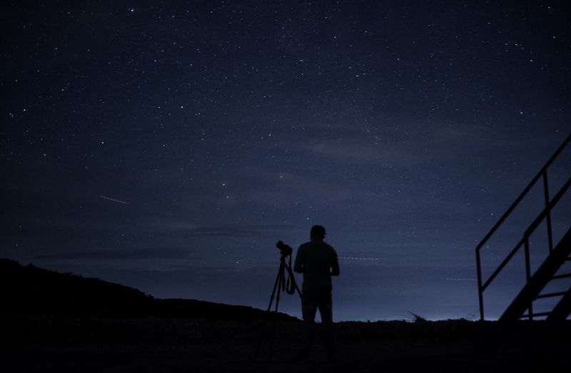 Silhouette man with camera and tripod standing against sky at night