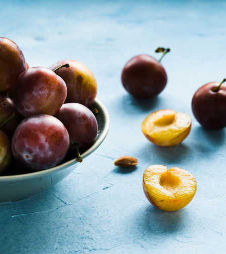 plums cutted in halfs on a bright background | daylight foodphotography martin willmann Bright Shadows & Lights Blue Close-up Cutted Daylight Photography Focus On Foreground Food Food Photography Foodphotography Fruit Healthy Eating Large Group Of Objects Light And Shadow Nikonphotography No People Plum Purple Ready-to-eat Still Life Vegetable Yellow