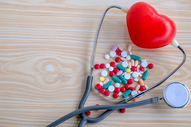 Concept of heart disease treatment Care Check Doctor  Drug Hospital Life Medicine Pain Pharmacy Red Wellness Background Concept Disease Equipment Health Healthy Heart Illness Instrument Medical Stethoscope  Treatment White Wooden