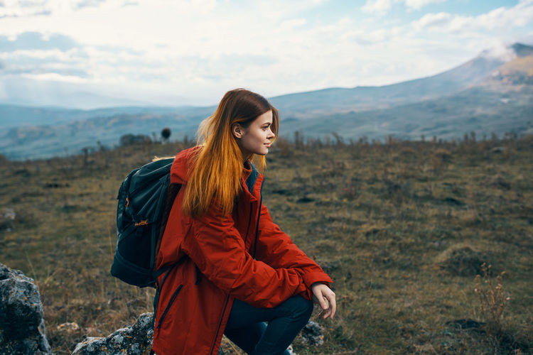 Young woman standing on land against sky