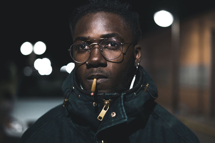 Close-up portrait of young man smoking marijuana joint at night