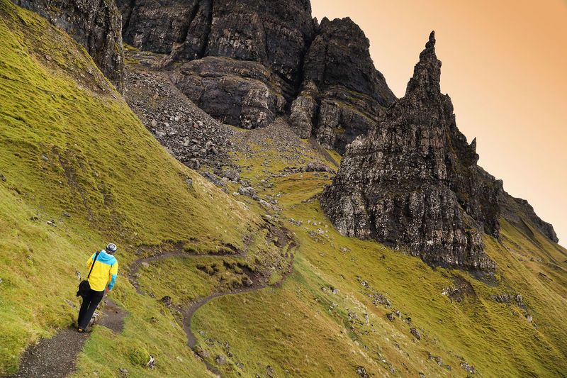 Rear view of man walking on storr at isle of skye against sky during sunset