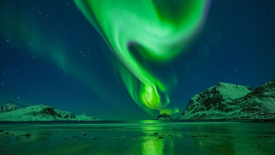 Aurora borealis over sea against sky at night