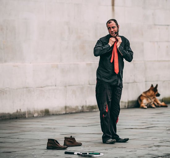 Full length of homeless man standing on footpath in city