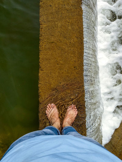 Low section of man standing by water