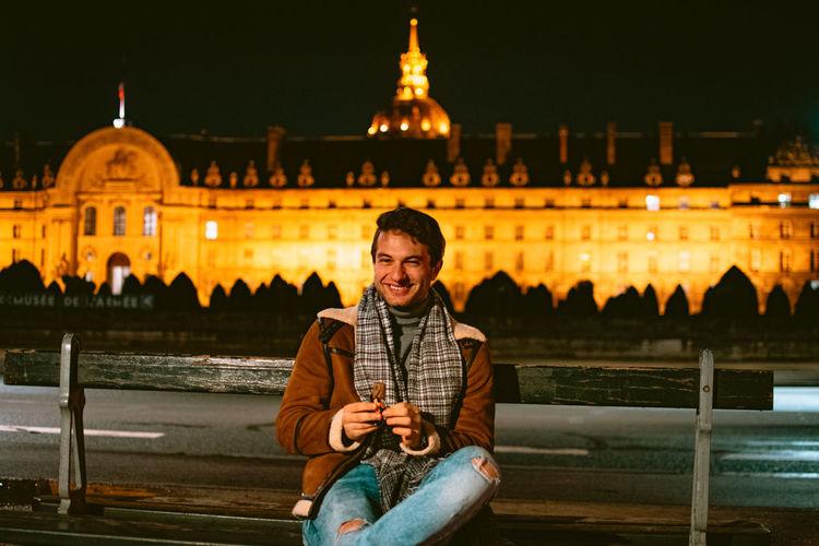 Young man sitting and eating sweets at illuminated city at night