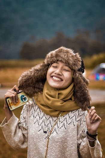 Smiling young woman wearing warm clothing on field