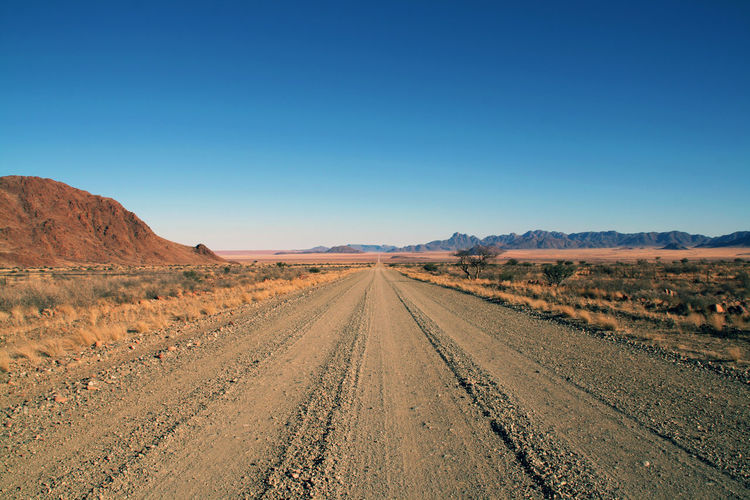 Africa Arid Climate Beauty In Nature Blue Clear Sky Country Road Desert Diminishing Perspective Dirt Road Extreme Terrain Landscape Mountain Namib Desert Namibia Nature Nature Non-urban Scene Outdoors Remote Road Scenics Surface Level Tranquil Scene Tranquility Vanishing Point