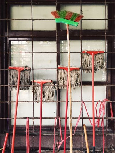 Mops And Broom At Metal Grate Of Closed Window