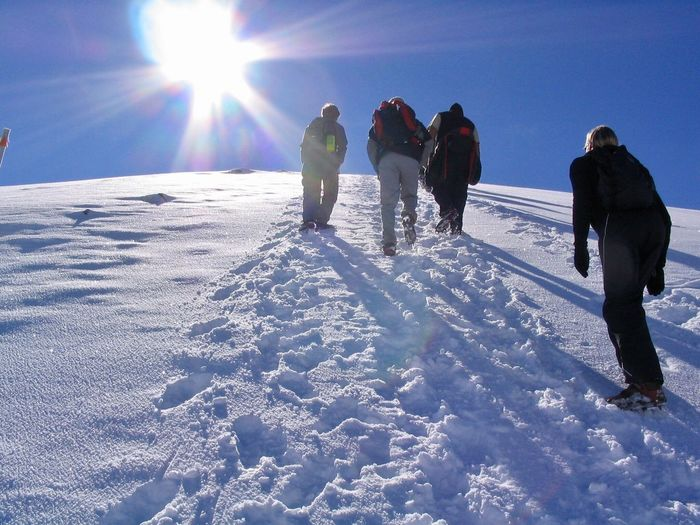People On Snowcapped Mountain Against Sky During Sunny Day