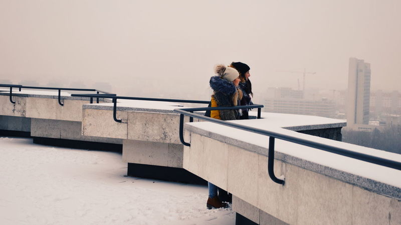 Urban Urban Perspectives Urban Scene Street Streetphotography Street Scene City Young Women Warm Clothing Togetherness Women Bonding Full Length Friendship Happiness Standing Snow Covered