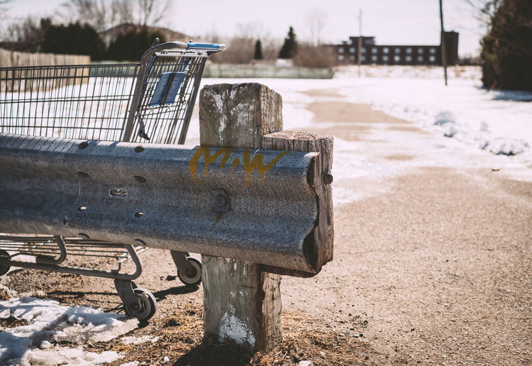 Shopping cart by railing on ground during winter