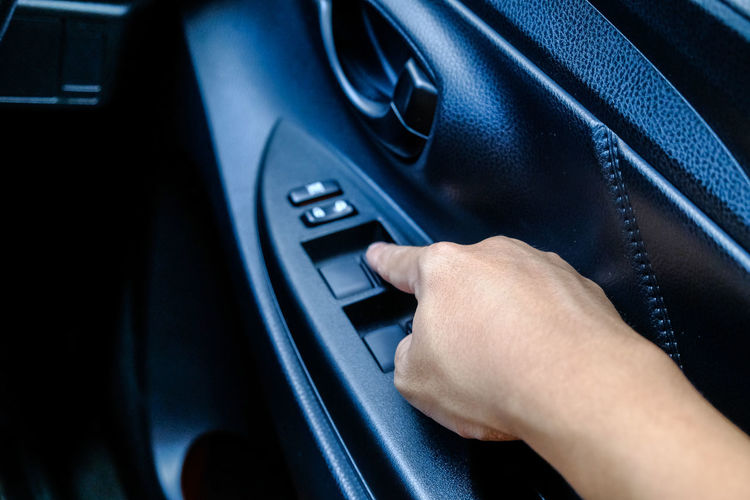 Cropped hand touching push button on car door