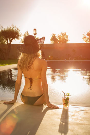 Rear View Of Woman Sitting On Swimming Pool During Sunset