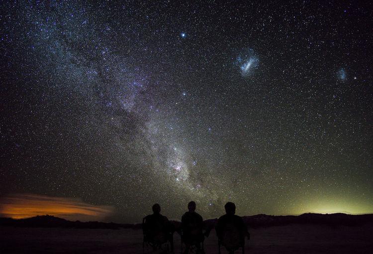 Silhouette male friends sitting on landscape against star field