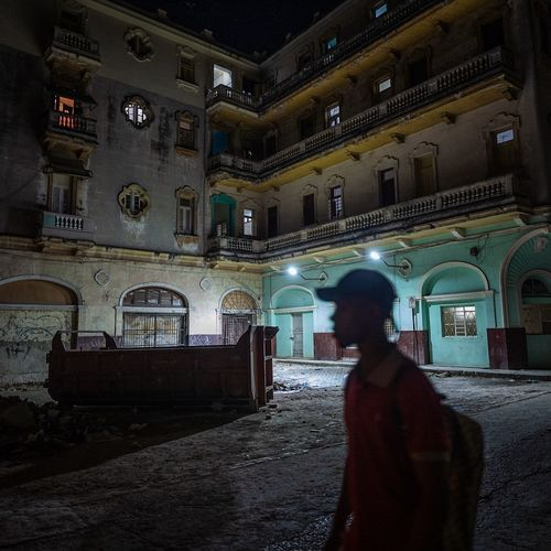 Rear view of man walking in building at night