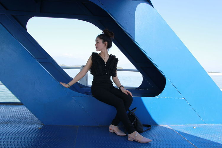 Full length of young woman sitting on metallic built structure on ship in sea against blue sky