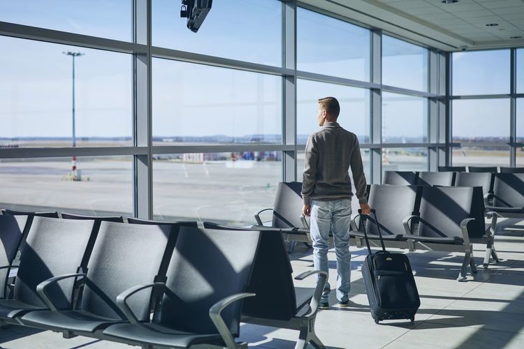 Traveler in airport terminal. Young man with luggage waiting for airplane. Airport Airport Terminal Departure Travel Men People Young Men One Person Window Real People Airport Departure Area Transportation Seat Business Journey Vacations Waiting Young Adult Luggage Suitcase Looking Through Window Contemplation Lonely Passenger Full Length