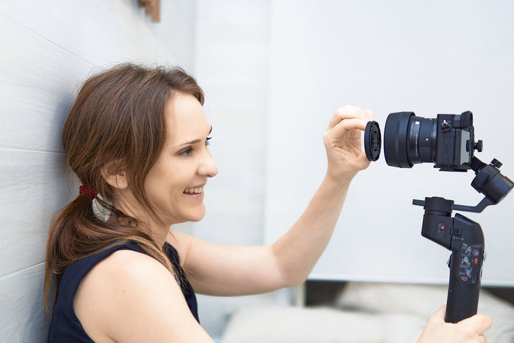 Woman sitting at home recording a blog for video media platforms with mirrorless camera gimball