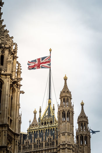 Low angle view of british flag on houses of parliament against sky