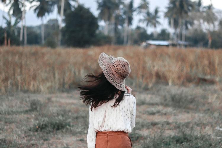 Rear view of woman wearing hat standing on field