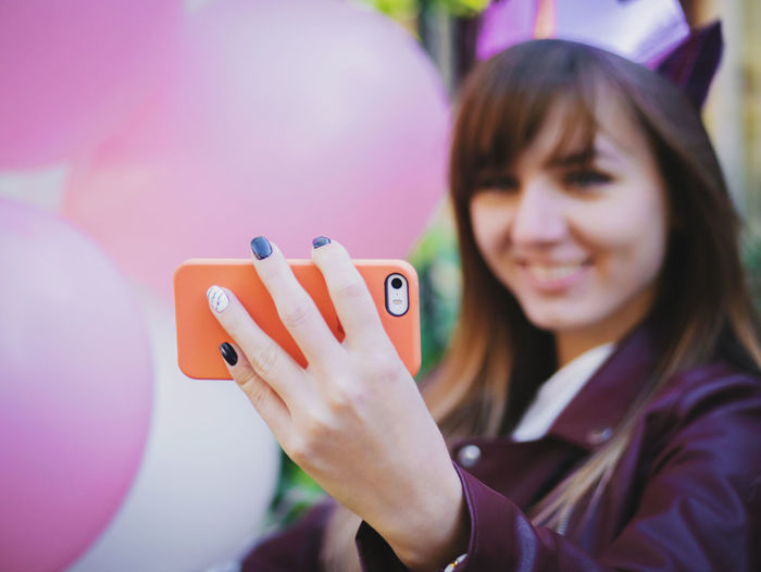 Smiling young woman taking selfie