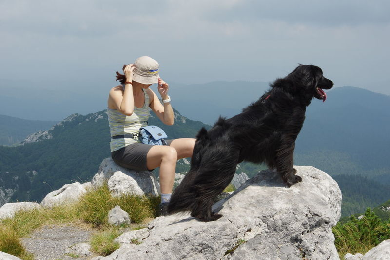 Woman Sitting With Flat-Coated Retriever On Mountain Peak Against Sky