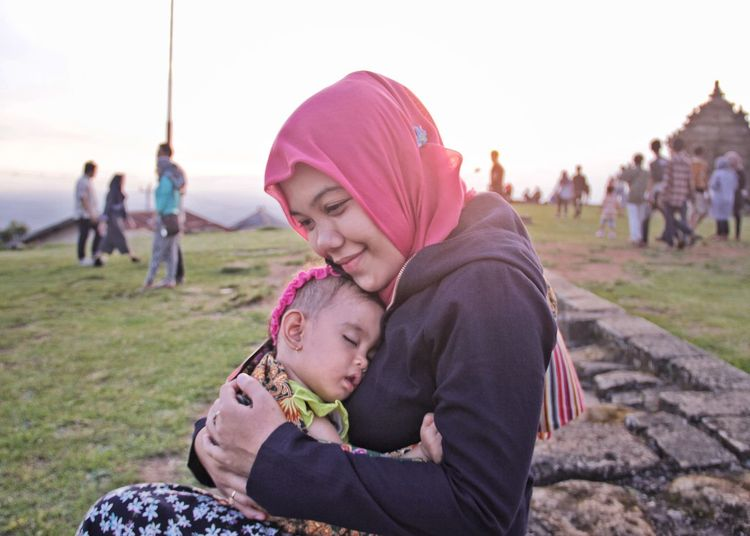 Side view of mother with cute sleeping daughter sitting on field against clear sky at park