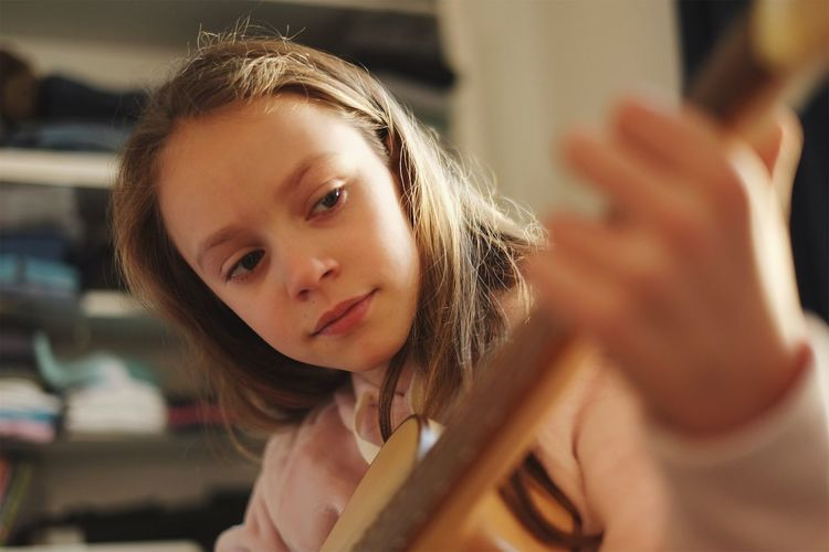 Close-up portrait of girl playing guitar
