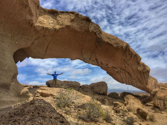 Man Standing Under Rock Formation Against Sky