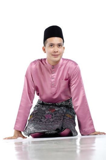 Portrait of young and handsome asian man with traditional clothing during hari raya over white background Studio Shot White Background Looking At Camera One Person Front View Portrait Indoors  Sitting Young Adult Clothing Cut Out Three Quarter Length Confidence  Full Length Pink Color Waist Up Young Men Standing Hairstyle