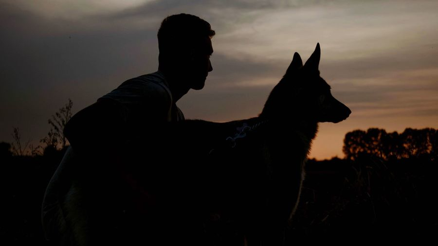 Silhouette One Animal Domestic Animals Sunset Animal Themes One Person Pets Dog Sky Mammal Real People Outdoors Side View Lifestyles Nature Sitting Day Adult People Pet Portraits