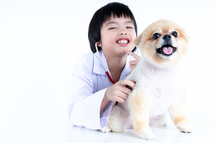 Isolated portrait of young female veterinarian with eyeglasses checking up Pomeranian dog in veterinary clinic. Studio shot of girl and puppy on white background Animal Themes Pets Domestic Animal Mammal Portrait Dog Canine Looking At Camera Studio Shot Front View White Background Veterinarian Clinic Hospital Healthy Eating Smiling Stethoscope