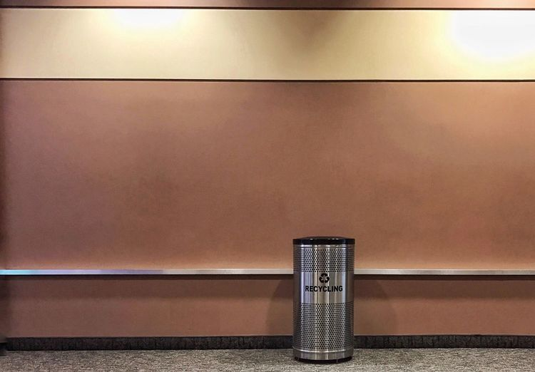 Metallic dust bin against wall