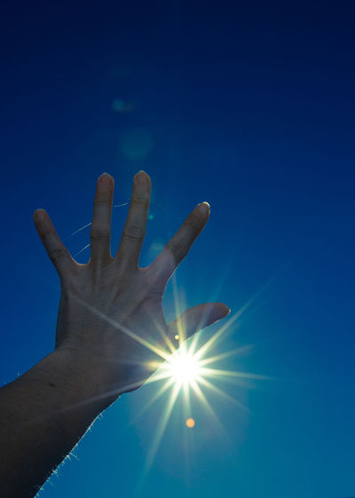 Cropped image of hand against sun shining in sky