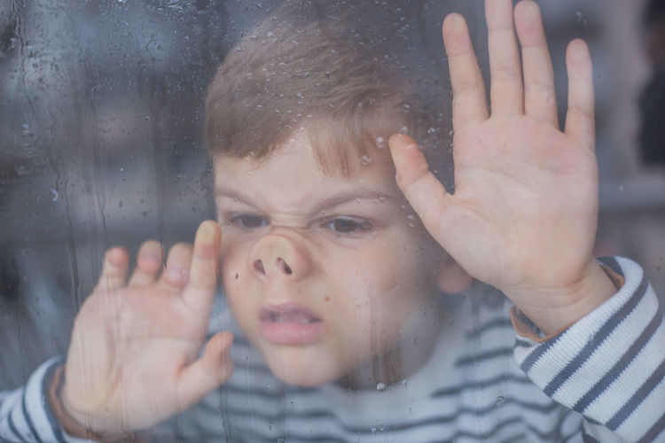 Close-Up Of Boy Looking Through Wet Window During Rainfall
