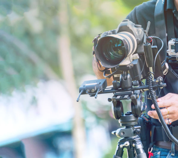 Midsection of man using television camera while standing outdoors