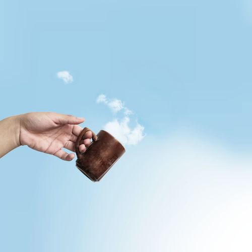 Cropped Hand Holding Mug Against Cloudy Sky