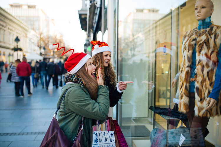 Two young attractive woman with santa claus hat in front of shopping window looking to buy something. Boutique Business Sale Standing Window Shopping Buying Consumerism Customer  Gift Lifestyles People Real People Retail  Retail Display Santas Hat Shopaholic Shopping Shopping Bag Shopping Mall Store Store Window Street Window Young Adult Young Women