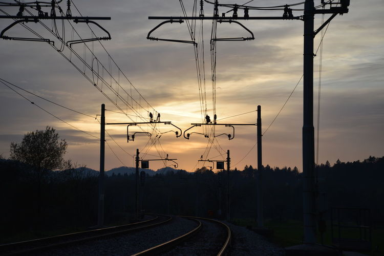 Silhouette railroad tracks against sky during sunset