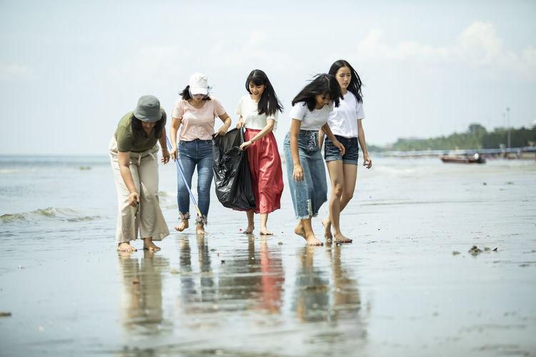 Group of people walking on beach against sky