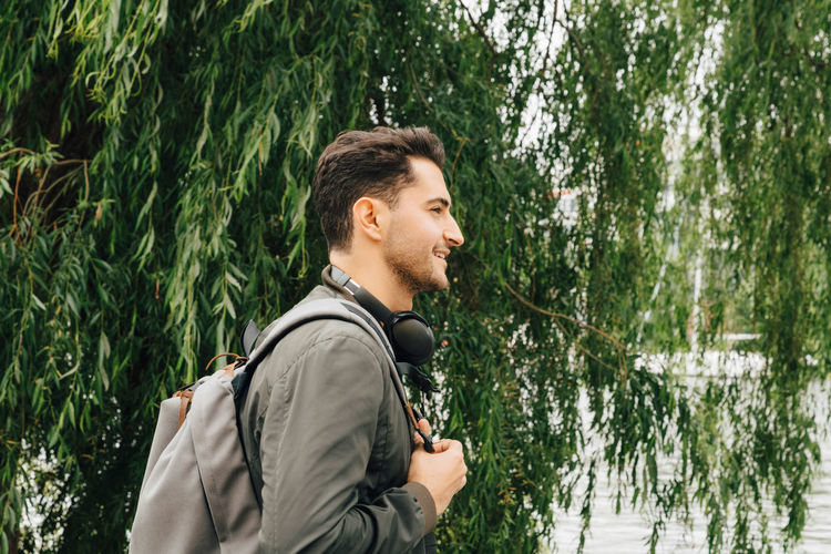 Side view of young man looking away against trees