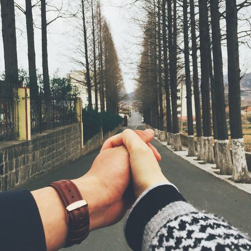 Cropped image of couple holding hands on road