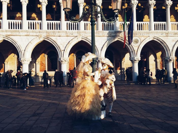 Man and woman in costume during venice carnival on street