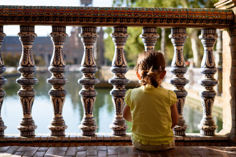 Rear view of small child sitting on a step at the Plaza de Espana in Sevilla, Spain Sitting The Week On EyeEm Travel Traveling Architecture Built Structure Child Childhood Day First Eyeem Photo One Person Outdoors People Rear View Travel Destinations Fresh On Market 2017
