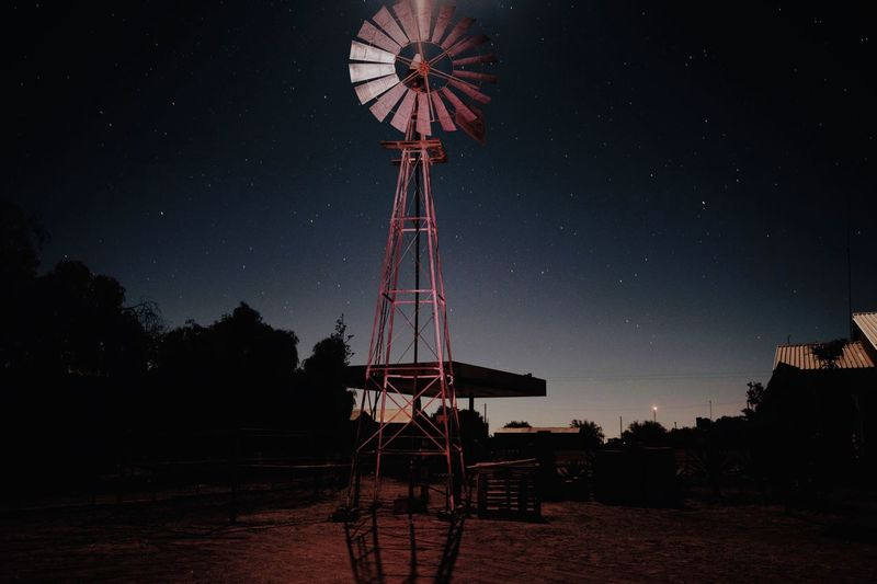 Low angle view of american style windmill on land against sky at night