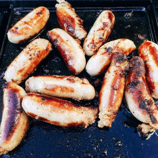 Sausages cooking on hot plate Sausages Cooking Browning BBQ Barbequed Golden Colour Meat Hot Plate Griddle Food