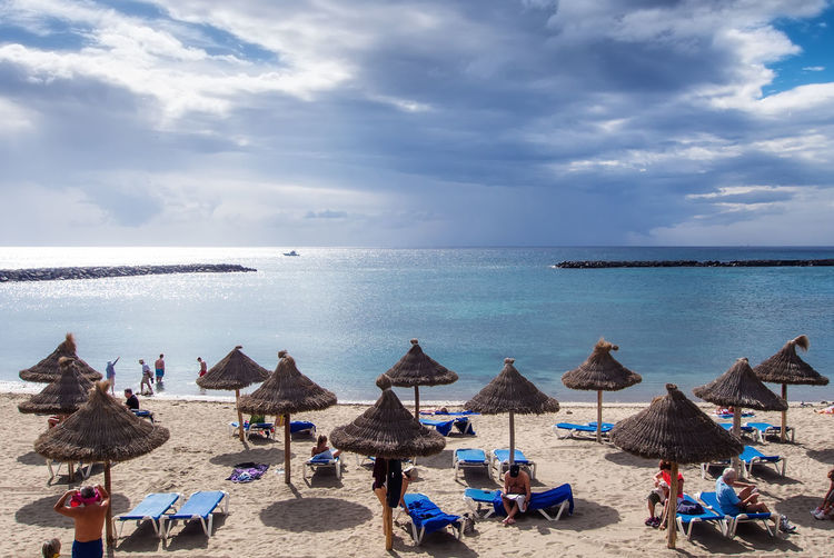 Tenerife, Canary Islands- January 09, 2015: People sunbathing on the Las Americas coast, one of the most popular and well-known resorts in Tenerife. Canary islands, Spain Atlantic Ocean Deck Chair Dramatic Sky Holiday Moody Sky Parasols Swimming Vacations Beach Beach Umbrella Cloud - Sky Coast Horizon Over Water Landscape Nature People Sand Sea Sun Lounger Sunbath Sunbathing Tenerife Tenerife Island Travel Destinations Water