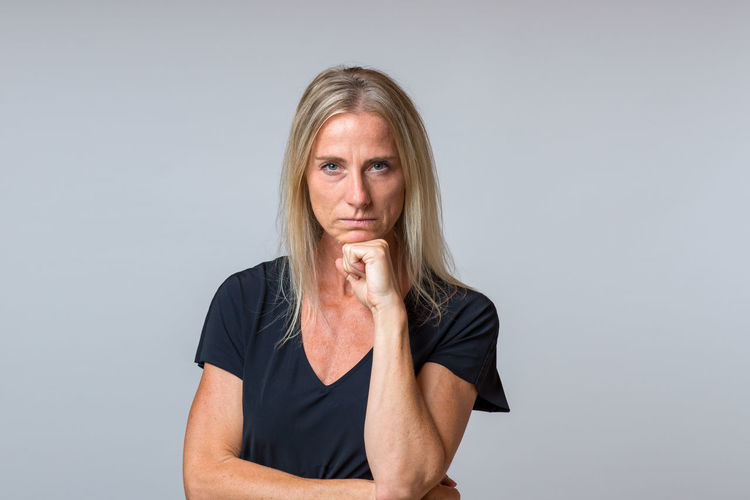Portrait Of Mature Woman Standing Against Gray Background